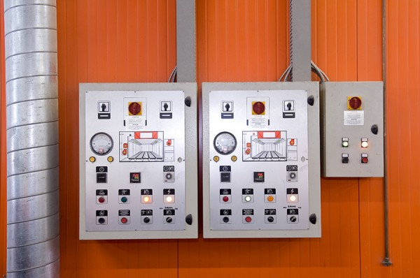 Ventilation control panels on wall of spray booth in automotive body shop